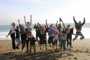 queer students at camp, jumping on a beach